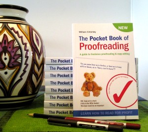 A copy of the Pocket Book of Proofreading with some pens