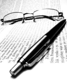 Spectacles and a pen lying on a book